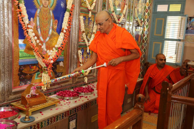 Acharya Swamishree showers Shree Ghanshyam Maharaj with coloured water