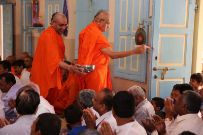 Acharya Swamishree showers coloured water onto sants and disciples