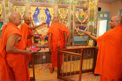 Acharya Swamishree is showered with coloured water and power