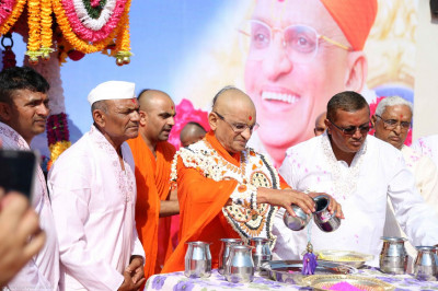 Acharya Swamishree bathes Shree Harikrishna Maharaj with coloured water