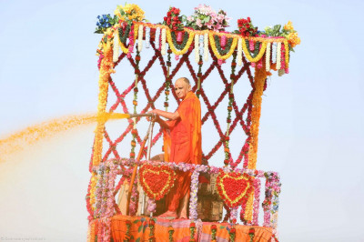 Acharya Swamishree sprays coloured water on to disciples