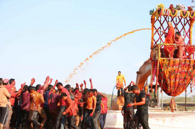 Acharya Swamishree continues to spray coloured water