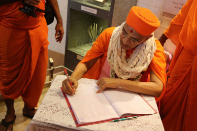 A guest book is signed by Acharya Swamishree Maharaj