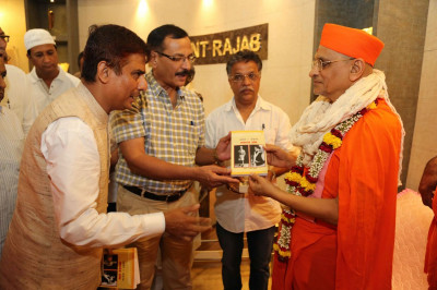 Acharya Swamishree Maharaj presents books to guests