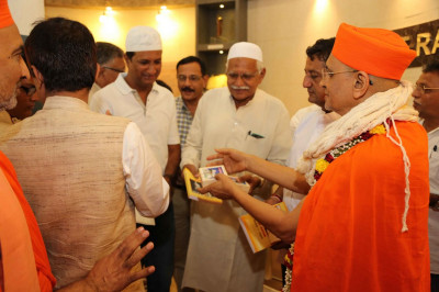 Acharya Swamishree Maharaj offers prasad to all