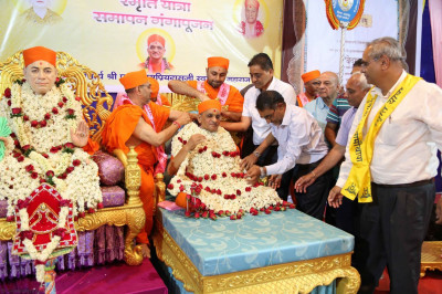 Sants and disciples put a flower garland on Acharya Swamishree
