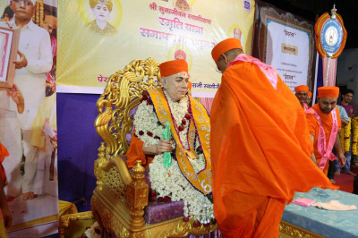 Acharya Swamishree offers a garland to Jeevanpran Swamibapa that has been inscribed with the honorary titles given to Him in 1973 during the Mokshdayi Yatra by the scholars of Kashi