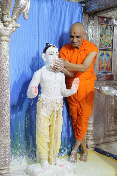 Acharya Swamishree bathes Lord Swaminarayan with yougurt