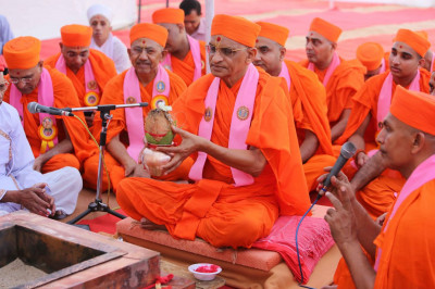 Acharya Swamishree holds a kalas and coconut