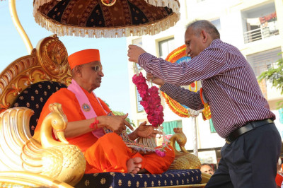 A disciples puts a garland on Acharya Swamishree during the start of a procession