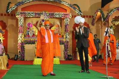 His Divine Holiness Acharya Swamishree is escorted onto the stage by world famous singer Jeffrey Iqbal
