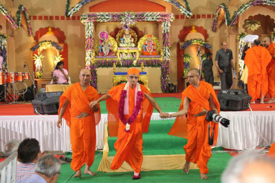 His Divine Holiness Acharya Swamishree is escorted from the stage by Sants