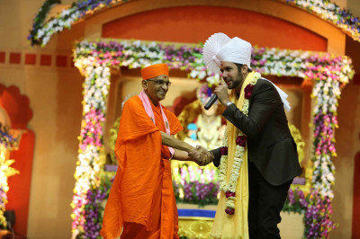 His Divine Holiness Acharya Swamishree blesses Jeffrey Iqbal on stage