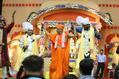 His Divine Holiness Acharya Swamishree dances on stage as the artists sing devotional songs