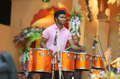 Artists accompany singers singing devotional songs by playing various drums
