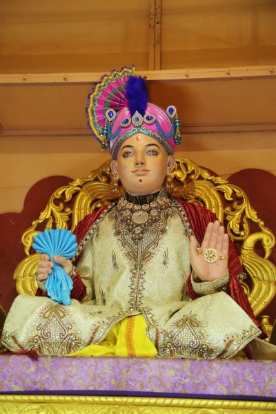 Divine darshan of Lord Shree Swaminarayan seated on Shree Swaminarayan Gadi on the charming village style stage
