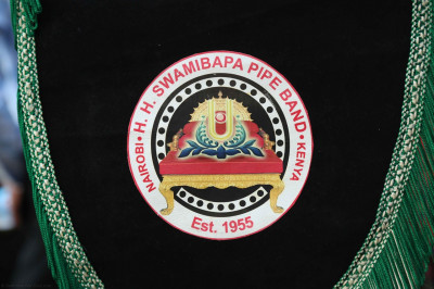 A close of the H. H. Swamibapa Pipe Band Nairobi badge with the tilak chandlo on Shree Swaminarayan Gadi