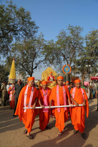 Sants pull the golden chariot as His Divine Holiness Acharya Swamishree blesses all during the street procession