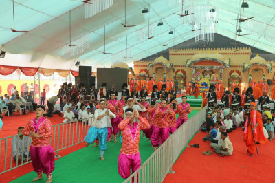 Disciples perform an energetic dance welcoming His Divine Holiness Acharya Swamishree onto the stage