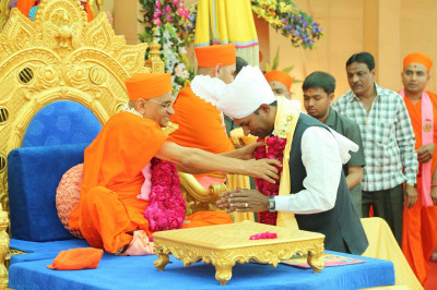 His Divine Holiness Acharya Swamishree presents a prasad paag, a prasad shawl and a garland of roses to the honoured guest