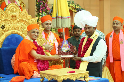 His Divine Holiness Acharya Swamishree presents a momento of the festival to the honoured guest