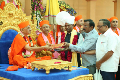His Divine Holiness Acharya Swamishree is presented with items to be inaugurated