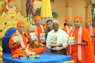His Divine Holiness Acharya Swamishree releases the publication 'Khedanu Sahubhagya' and presents to Sants and disciples