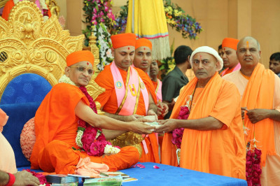 His Divine Holiness Acharya Swamishree presents prasad to the honoured Sadhus from the nearby Santram Mandir