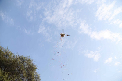 A helicopter drone showers fresh fragrant flowers on all during the grand procession