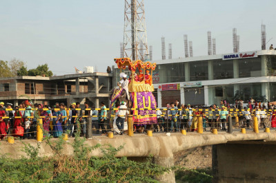 The procession proceeds over the bridge spanning the Vatrak river