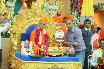 His Divine Holiness Acharya Swamishree is presented with various gifts by members of organisations that support relief efforts during times of natural disasters