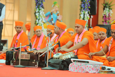 Talented sants play various instruments accompanying devotional songs during His Divine Holiness Acharya Swamishree's divine blessings