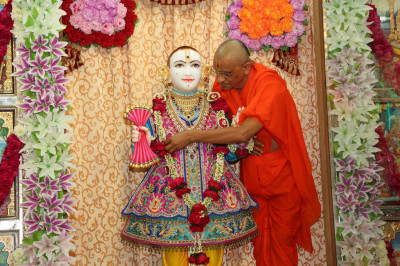 His Divine Holiness Acharya Swamishree showers Lord Shree Swaminarayan with gold and silver flower petals
