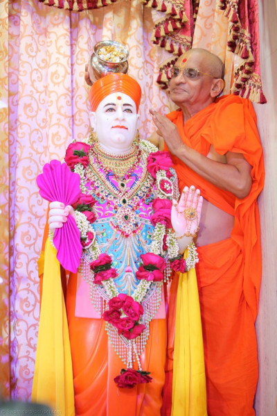 His Divine Holiness Acharya Swamishree showers Jeevanpran Shree Muktajeevan Swamibapa with gold and silver flower petals