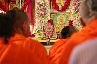 Divine darshan of Shree Harikrishna Maharaj adorned in bright pink and intricate garlands made entirely from various nuts and seeds
