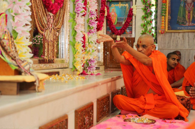 His Divine Holiness Acharya Swamishree offers the silver and golden flowers to the lotus feet of the Lord