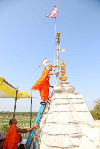 His Divine Holiness Acharya Swamishree climbs to tallest shikkar and hoists up the new mandir flag