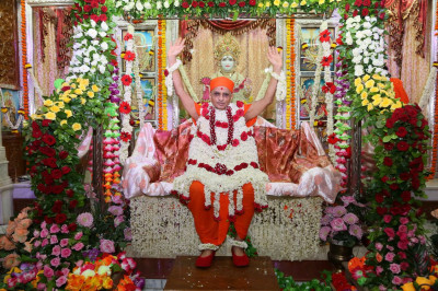 Divine darshan of Acharya Swamishree Maharaj seated on a swing