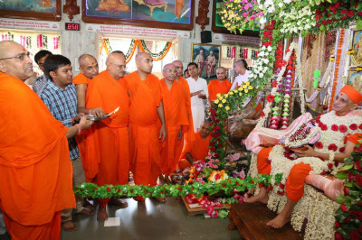 Sants and disciples perform aarti to Acharya Swamishree Maharaj