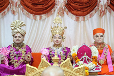 Shree Ghanshyam Maharaj, Jeevanrpan Bapashree, and Jeevanpran Swamibapa give darshan in the sabha mandap