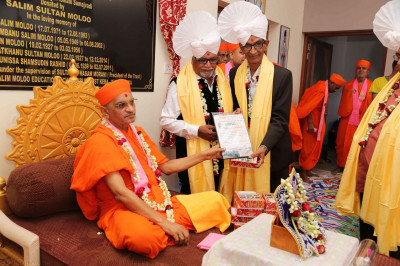 A thank you letter is presented to Acharya Swamishree