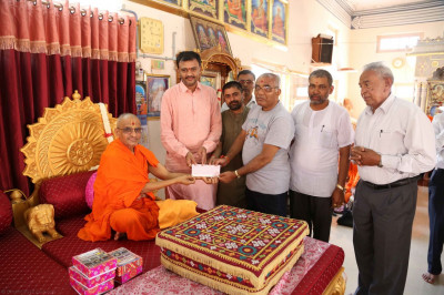 Acharya Swamishree makes a donation to a school