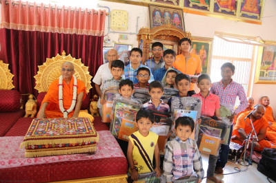 School children receive school bags from the sanstha
