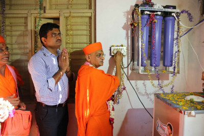 Acharya Swamishree inaugurates a water purification system donated by the sanstha for the school