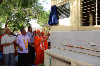 Acharya Swamishree unveils a plaque for the water purification system