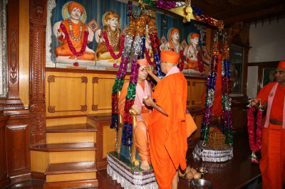 Acharya Swamishree Maharaj impress a chandlo on Jeevanpran Swamibapa at Shree Swaminarayan Tower