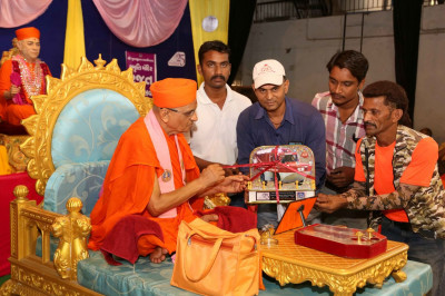 Acharya Swamishree Maharaj unveils a model of a rescue vehicle for use by Shree Muktajeevan Swamibapa Rescue and Disaster Management Academy