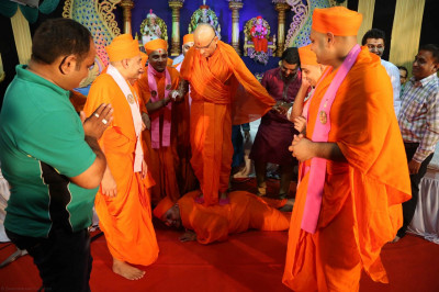 Sants escort His Divine Holiness Acharya Swamishree from the stage