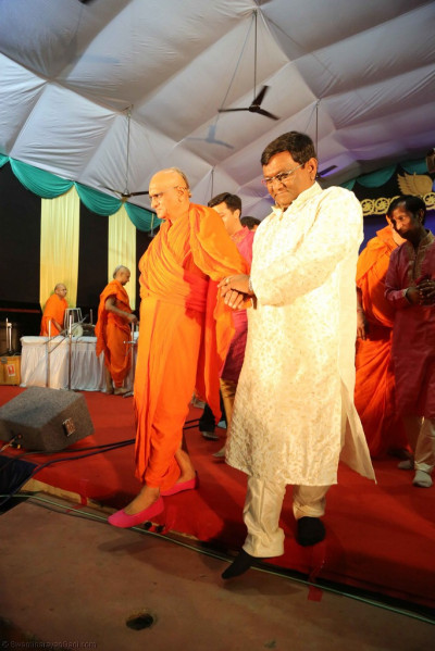 Disciples escort His Divine Holiness Acharya Swamishree from the stage