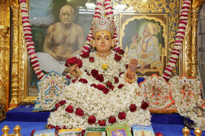 Divine darshan of Shree Sahajanad Swami adorned in garments made entirely of bright white flowers trimmed with deep red roses